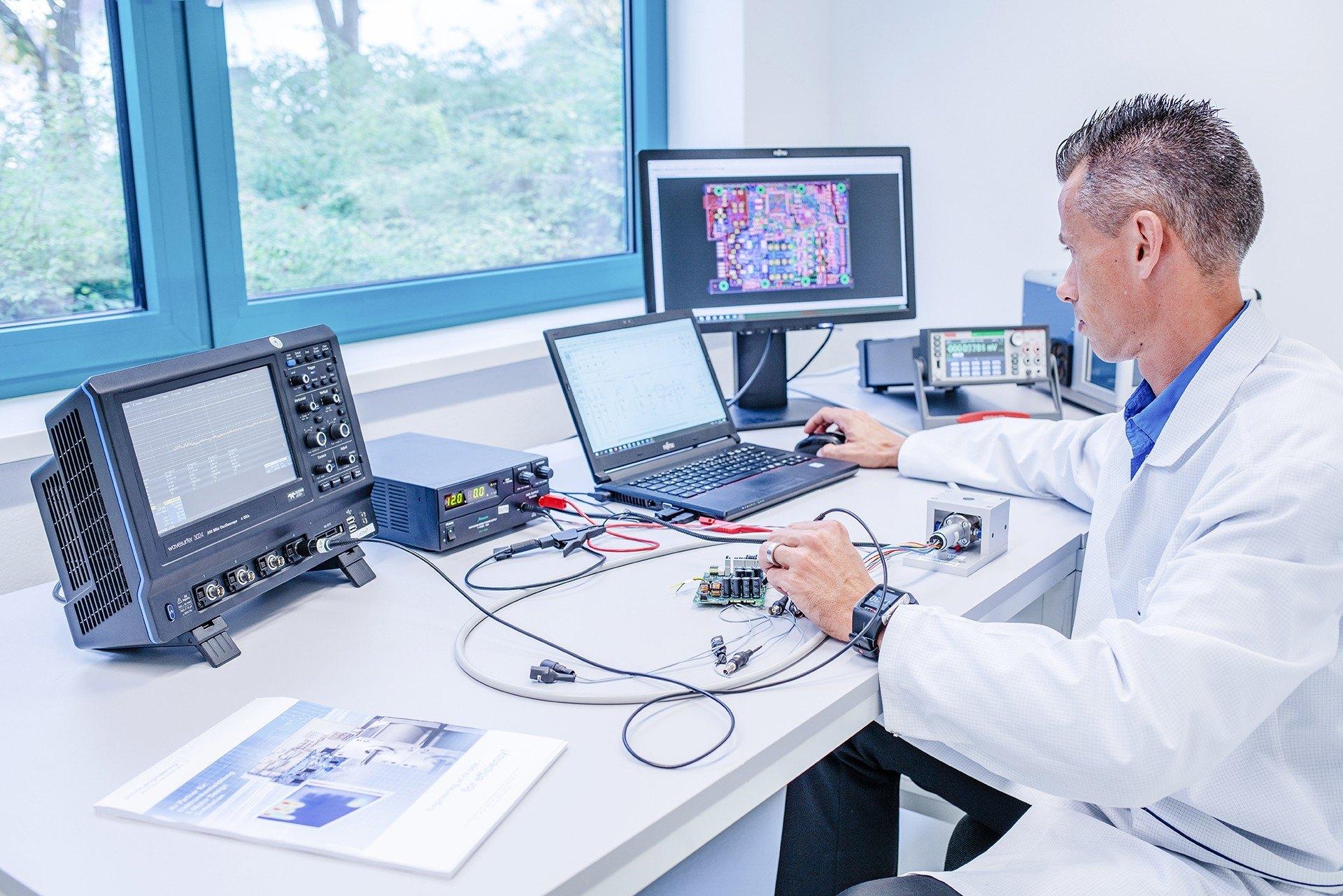 Ein Mann sitzt am Schreibtisch und kontrolliert ein hergestelltes Elektronikprodukt